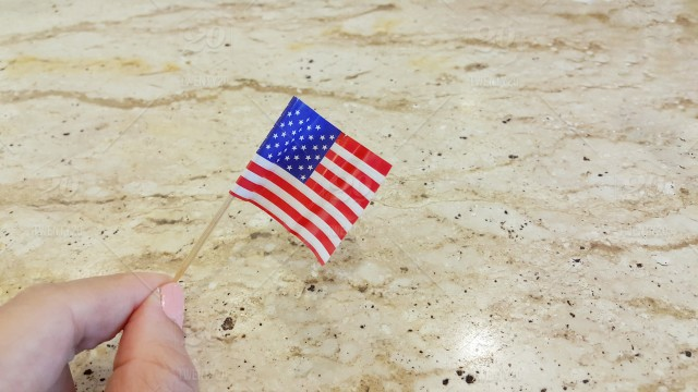 f69666b2572 Small American flag holding hand on table stock photo 03bc0634 ...