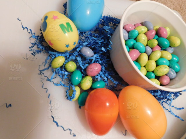 Easter A Bowl Of Colorful Chocolate Candy And Plastic Eggs Nestled In Blue Grass For Sweet Celebration Treat