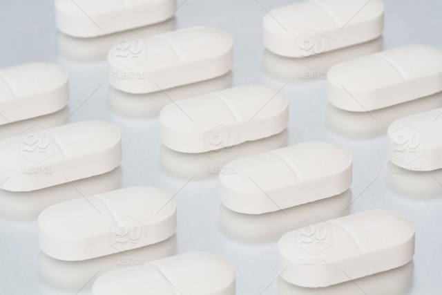 Rows and lines of white tablets, pills, drugs and medicines on an
