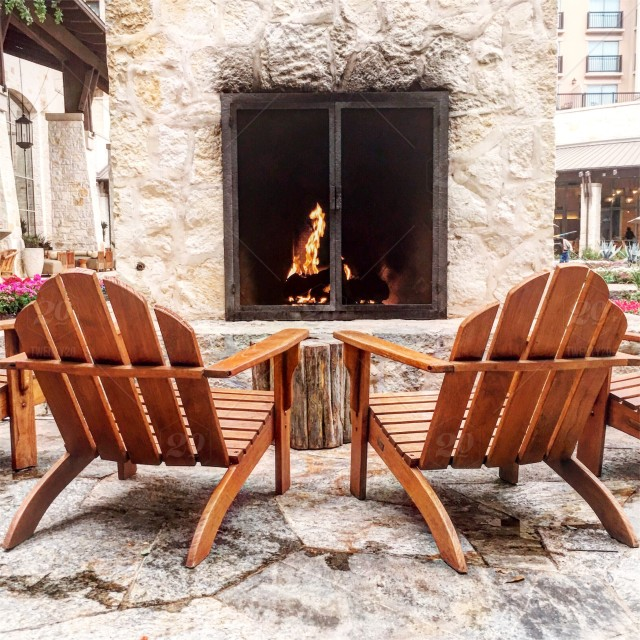 Two wooden chairs in front of stone fireplace stock photo ...