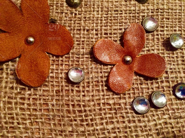 Leather flower cut outs on a burlap pin board with jewel push
