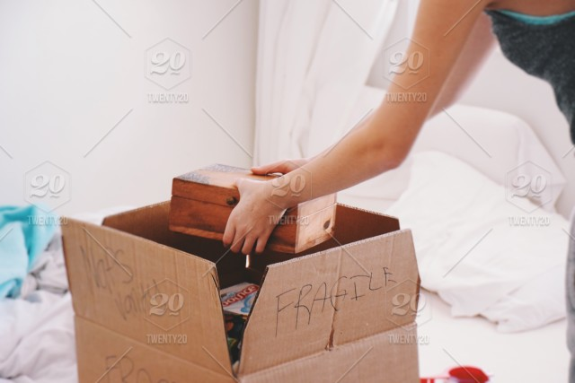 girl packing a box for moving stock photo 4a6a8034 63c0 49b6 ba2d