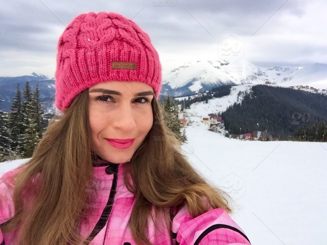 655925b33 Portrait of pretty woman wearing pink jacket and pink winter cap ...