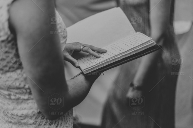 Digital high resolution close up black and white photograph of a woman reading a hand written journal while standing in a tent by dorey kronick