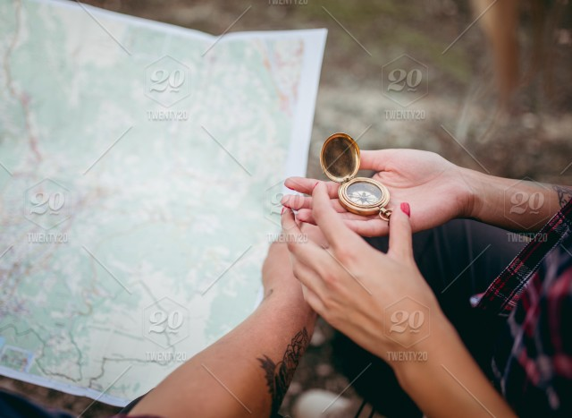 Couple planing travel route on map with compass stock photo