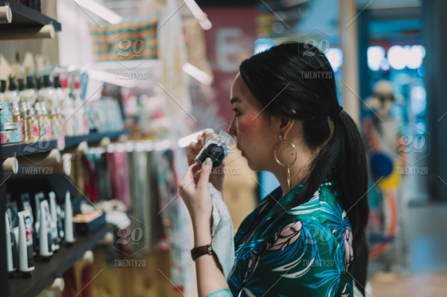 Woman smelling cosmetic stuff stock photo 6f01fae1-11ca