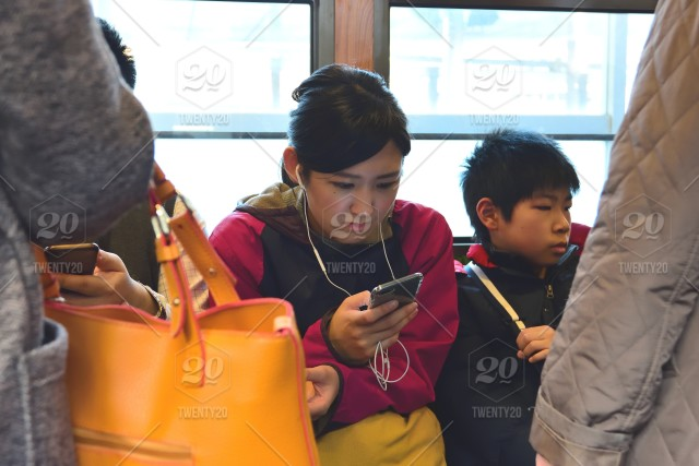 Japanese girl on her phone on the train stock photo 71014fff-91ca