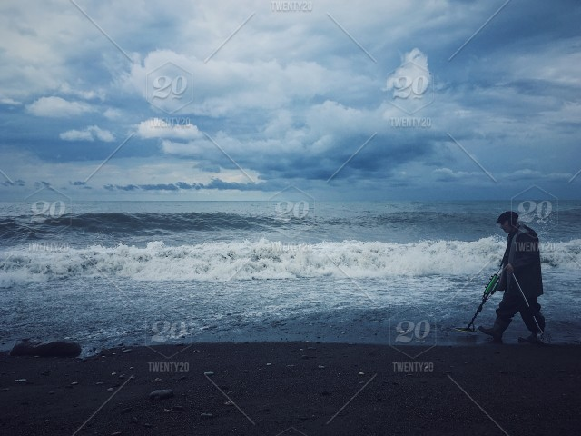 Black Sea storming  Man with a metal detector walking by the
