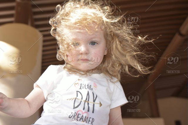 Toddler Girl With Blue Eyes Blonde Curly Hair Blowing In The Wind On A Sunny Day Outside Looking At The Camera