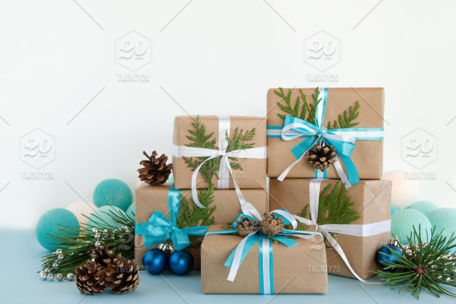 christmas gift boxes wrapped of craft paper blue and white ribbons on the blue and white background decorated of pine cones fir branches silver beads - Decorative Christmas Gift Boxes