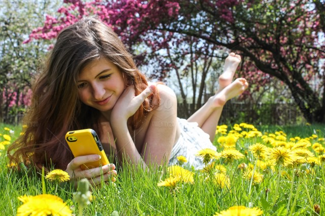 Happy Teen In Her Element Being A Teenager Techie Kid Millennial Life People Reading On Device Outside Moments Nature Outdoors Spring Flowers