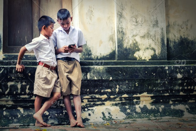 Two asian boys wearing school uniforms are playing game