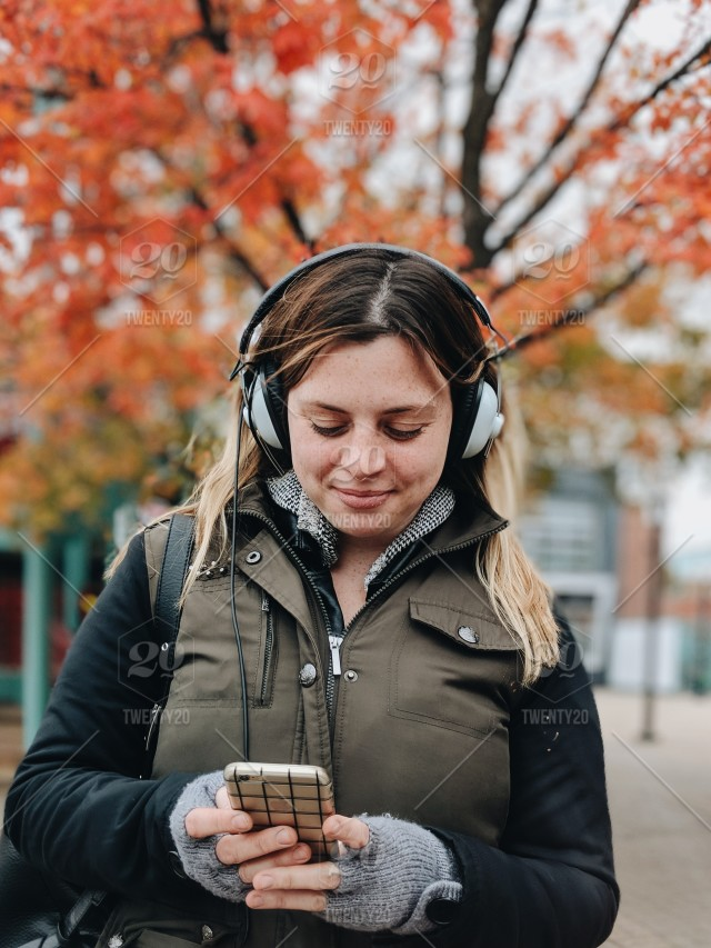 Woman in the fall using her phone and wearing headphones