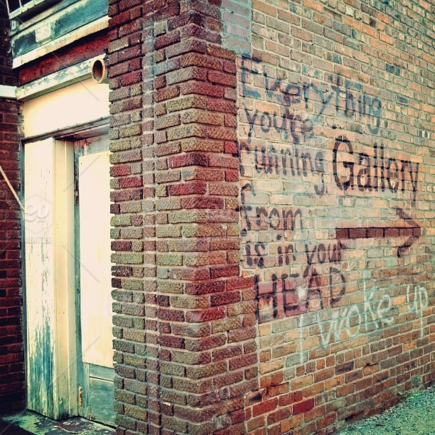 Sayings Spray Painted On A Brick Wall Leading Into An Alley Outdoor Art