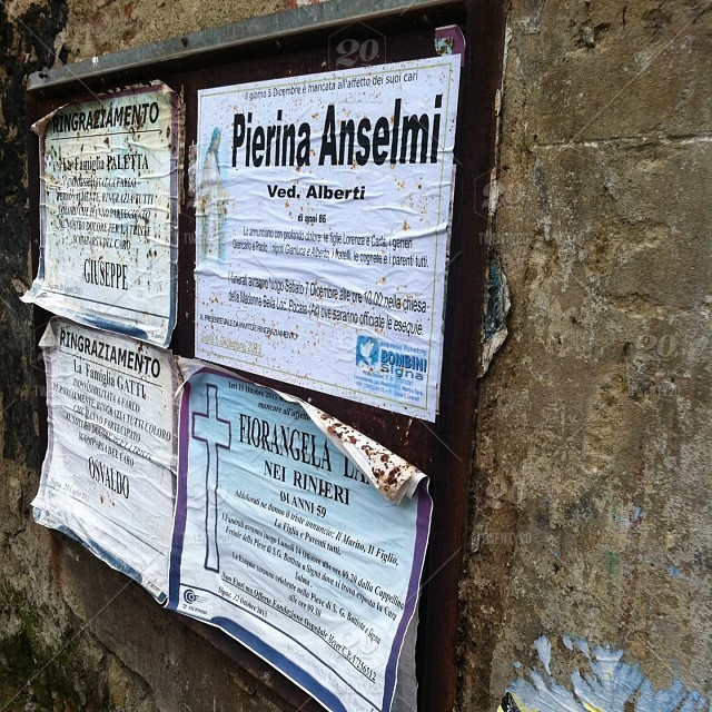 Funeral notices posted on a wall in Lecore, Tuscany, Italy stock photo