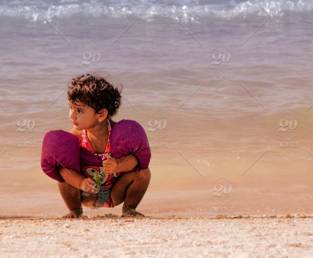 Hispanic Toddler Girl With Floats On Squats Down On The Edge Of