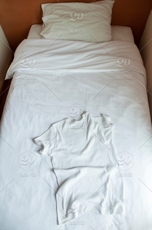 Top View Of White Cotton T Shirt On Single Bed In A Bedroom.