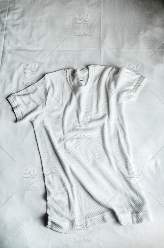 Top View Of White Cotton T Shirt Flat Lay On White Bed Sheet In A Bedroom.