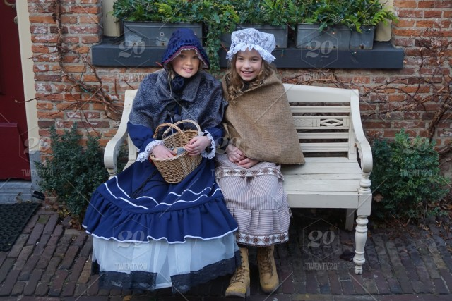 girls sitting on the bench during charles dickens festival at deventer