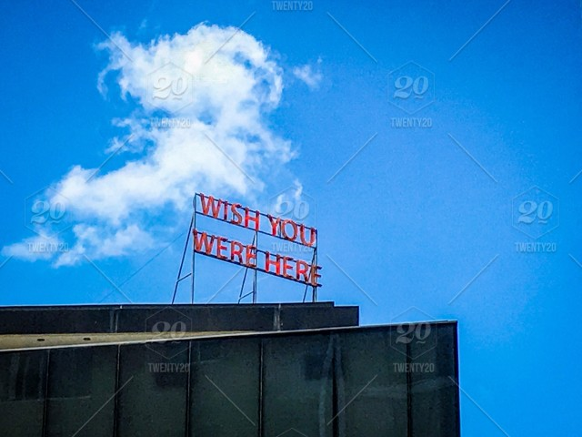 Wish You Were Here sign on top of a business stock photo 2b4d2119