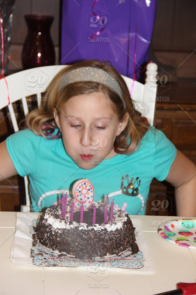 A Young Girl Happily Celebrates Her 9th Birthday By Blowing Out The