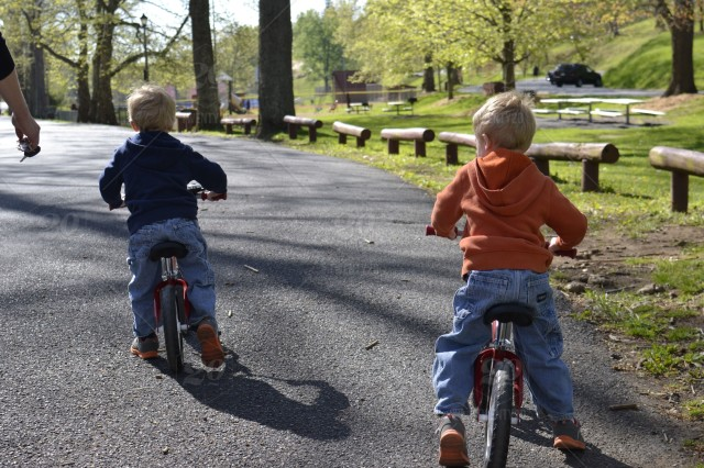 Two little boys learning how to ride their bikes at the park stock photo
