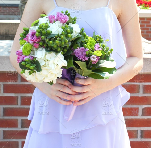 Holding a bouquet of purple, white and green wedding flowers. stock ...