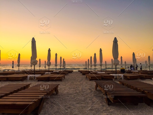 Wooden Sunbeds And Umbrellas On The Beach At Sunset Stock