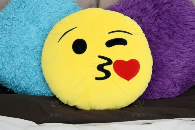 Kissy face emoji pillow on a bed  stock photo 78cdb923-e8bb