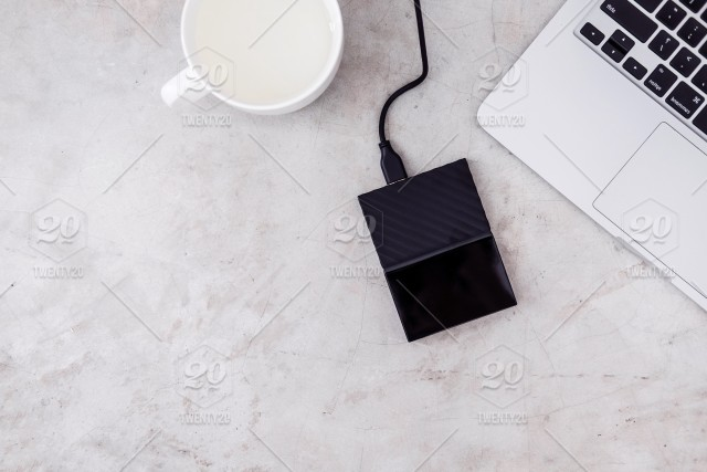 External hard drive connected to the laptop and white mug on