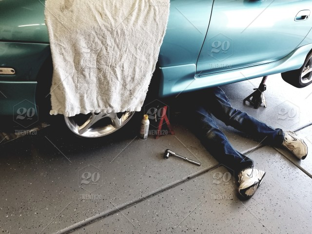 Auto mechanics a do it yourself garage mechanic under the vehicle auto mechanics a do it yourself garage mechanic under the vehicle working on his car solutioingenieria Choice Image