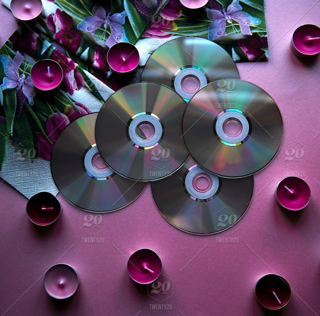 A full frame of cd's and pink purple candles on pink