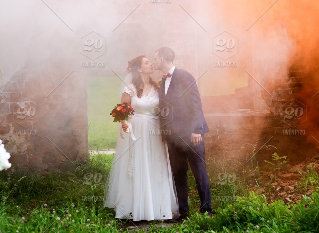 Bride and groom with the white and orange colored smoke