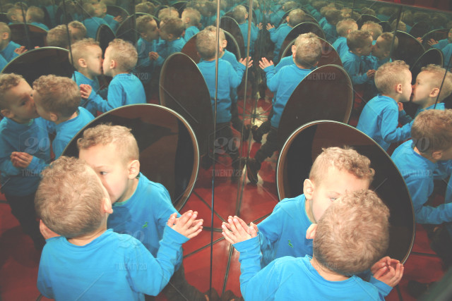 Toddler boy in mirror room - kissing himself - funny! stock