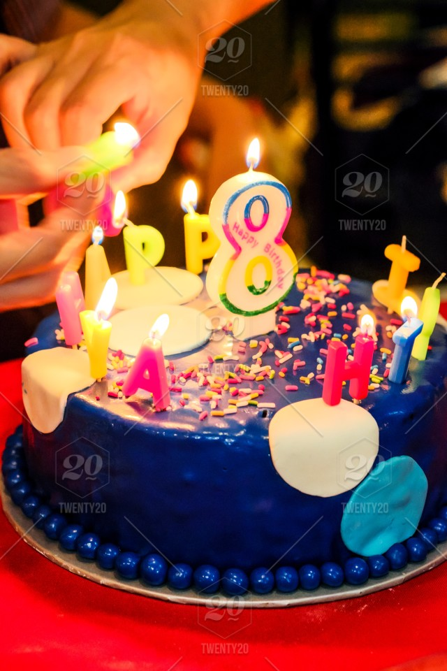 Close Up Of Lighting Candles On Birthday Cake For 8 Years Old Kid
