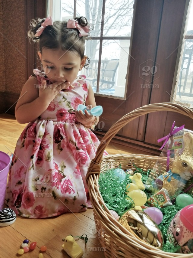 Hispanic Toddler Girl Dressed In Her Easter Dress And Hair Bows Eats