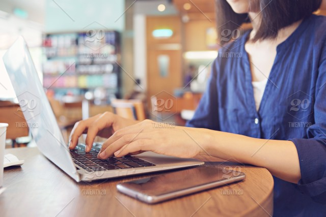 Women using smartphone and laptop, working at cafe stock photo