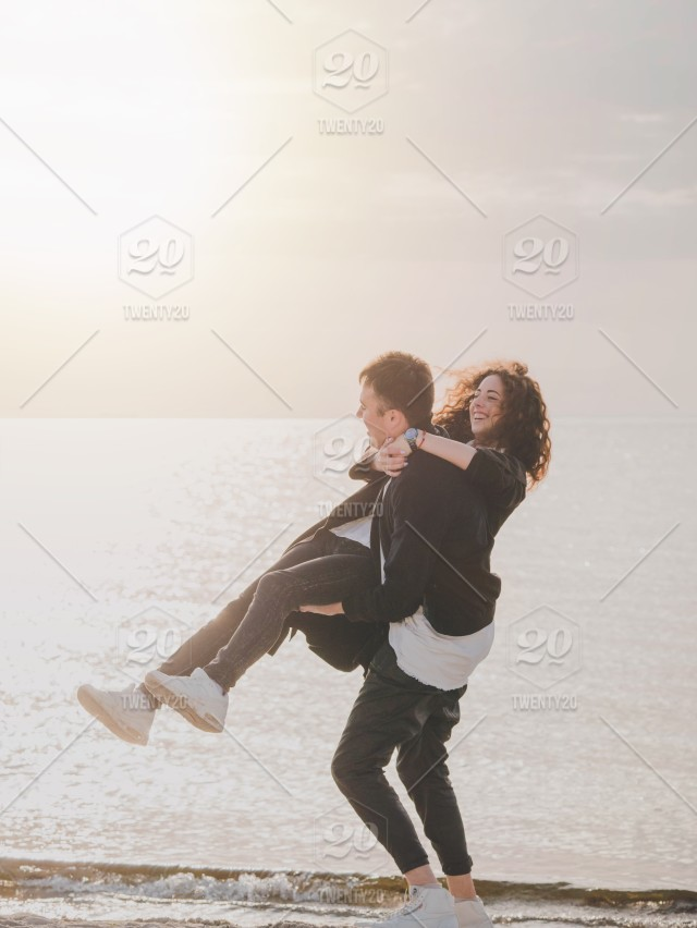 Young trendy man and woman, people on sand beach, happy married adult  couple having fun, playing, fooling by the sea in spring or autumn. Warm  sunny day.