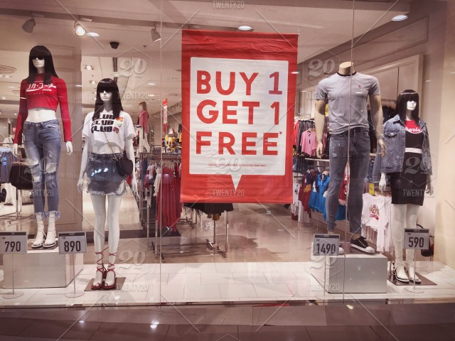 9e424fe7d6 SALE sign at a shopping mall. Buy 1 get 1 free. Retail shopping. Shop ...