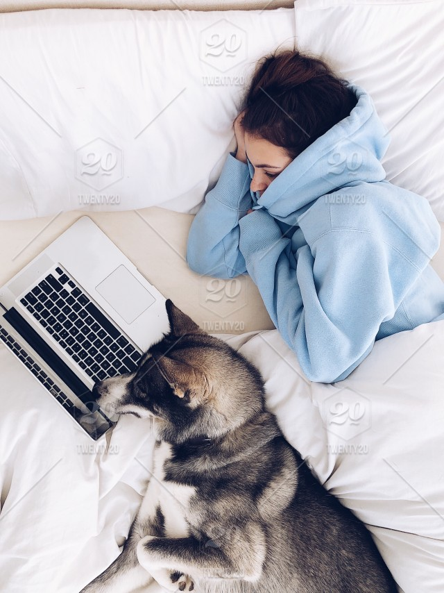 Young Teenage Girl And Her Cute Husky Dog Watching A Show On Netflix