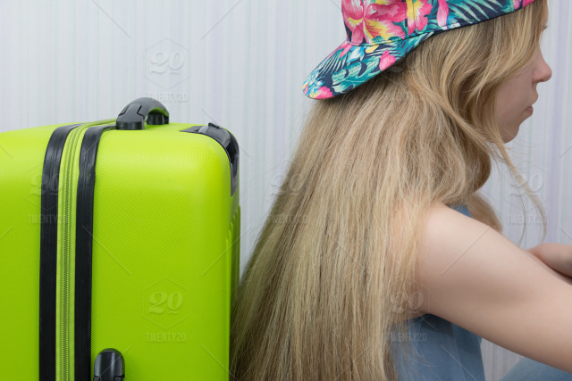3ba459f854 girl in a cap sits with her back to suitcase