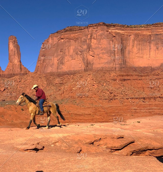 b44cf538db6 A man in a cowboy hat riding his horse in Monument Valley. stock ...