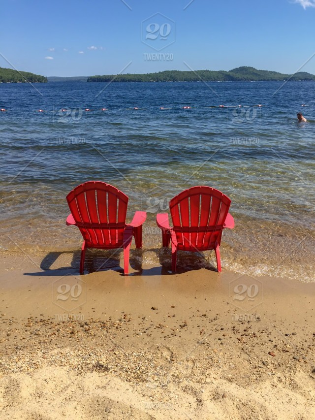 Two red beach chairs in the sand on the shore of a sparkling