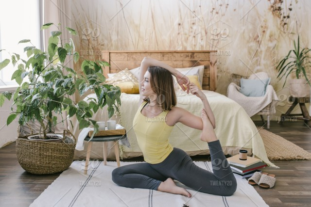 Woman Doing Yoga Exercise In Her Light Stylish Bedroom At Home
