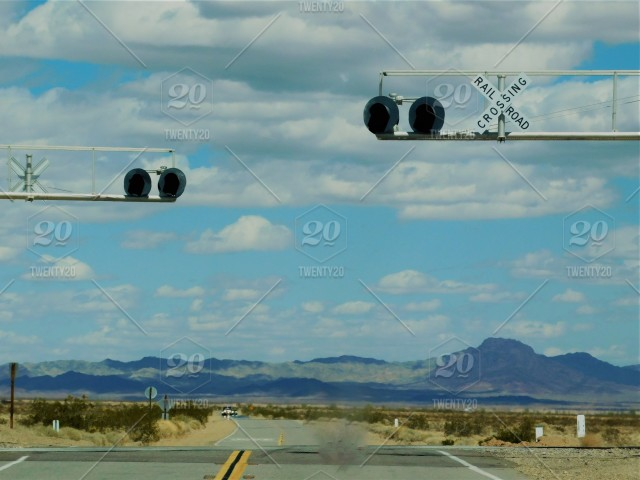The SKY! Railroad Crossing signs & flashing lights, across a