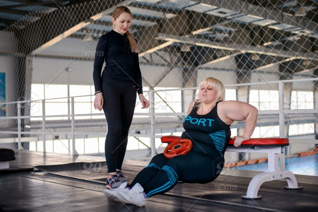 Fat woman trains in gym with a trainer, exercise to lose
