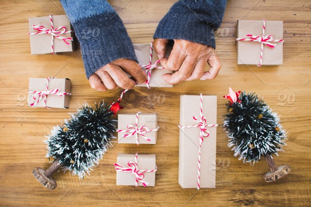 old female hand holding paper gift box with pine tree on brown wood background merry christmas and happy new year conceptselective and soft focus