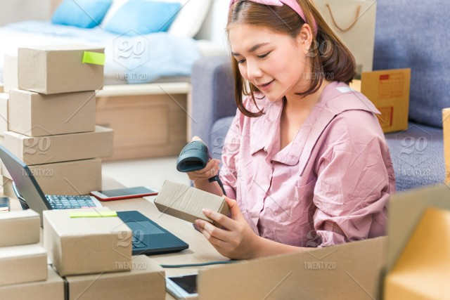 Young Asian female online seller using barcode scanner to scan her
