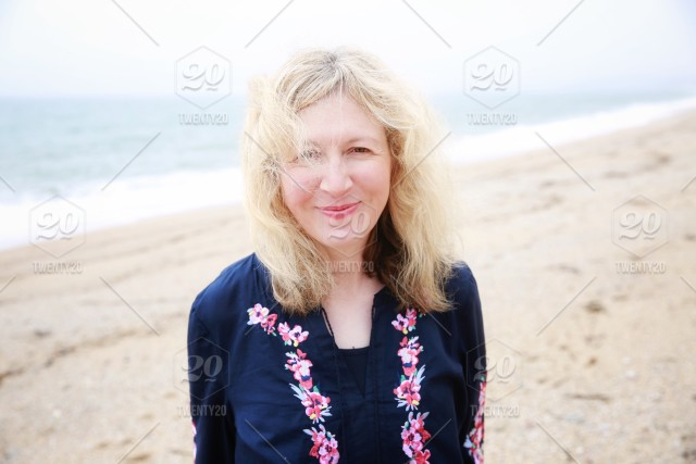 A Blonde Haired Woman Smiling Happily On A Sandy Beach With Windswept Hair Stock Photo E06ded17 4804 442f 9fc1 Df241545412d