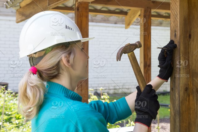 The girl hammers a nail with a hammer, real people, job